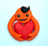 Plasticine smiling man with a big heart Stock Image
