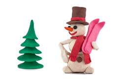 Plasticine snowman. With skis standing near the Christmas tree   on white background Royalty Free Stock Image