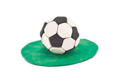 Plasticine soccer ball on grass. Plasticine football isolated on white background Royalty Free Stock Photo
