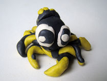 Plasticine spider made by child. Cute and smiling yellow and black plasticine spider mady by child Royalty Free Stock Images