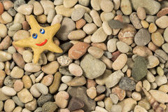 Plasticine star on sea shingle Stock Image