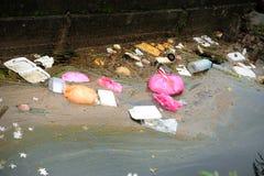 Plastiek en polystyreen snel voedsel verpakking in een rivier stock afbeeldingen