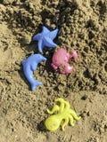 Plastiek gekleurde vormen in zand op het strand stock foto's