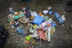 Plastik auf dem Strand mit Spritze und anderem Plastikabfall Lizenzfreie Stockfotos