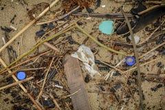 Plastik auf dem Strand mit Spritze und anderem Plastikabfall Stockbilder