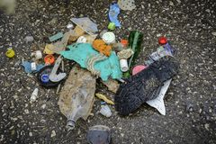 Plastik auf dem Strand mit Spritze und anderem Plastikabfall Stockbild