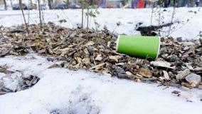 Plastik nimmt Kaffeetasse als Abfall auf Schnee weg lizenzfreie stockbilder