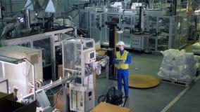 Plastik-produzierende Ausrüstung wird von einem männlichen Fachmann beobachtet stock video footage