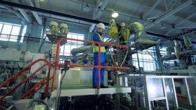 Plastik-produzierende Einheit mit einer männlichen Arbeitskraft, die auf einer Plattform steht stock footage