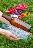 Plastik- und Glasflasche in der Hand der Frau, Abfall von Umwelt Lizenzfreies Stockbild