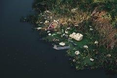 Plastik und Schaumabfall im Kanal stockfotografie