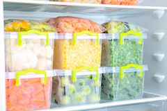 Plastikbehälter mit tiefgefrorenem Gemüse im Kühlschrank stockfoto