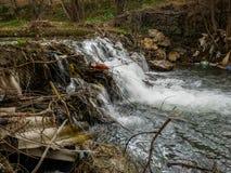 Plastikbierflasche im kleinen Wasserfall stockbilder
