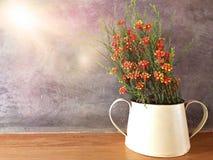Plastikblume im Glas auf hölzerner Tabelle mit Stuckwandhintergrund Stockfotografie
