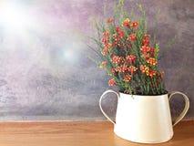 Plastikblume im Glas auf hölzerner Tabelle mit Stuckwandhintergrund Lizenzfreie Stockbilder