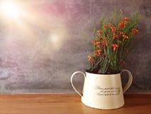Plastikblume im Glas auf hölzerner Tabelle mit Stuckwandhintergrund Stockfoto