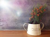 Plastikblume im Glas auf hölzerner Tabelle mit Stuckwandhintergrund Lizenzfreies Stockbild