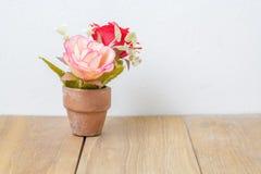 Plastikblume im Topf auf hölzernem Brett Lizenzfreies Stockbild
