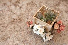 Plastikblumen mit Holzkisten Stockbilder