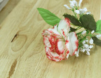 Plastikblumen und Plastikblatt setzten auf dem Tisch Holz lizenzfreie stockfotos