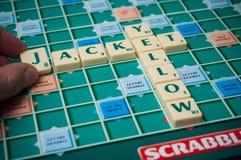 Plastikbuchstaben auf ScrabbleBrettspiel mit Wörtern: Gelbe Jacke stockfoto