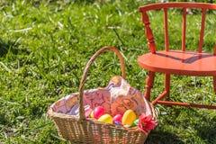 Plastikeier in Ostern-Korb, der in hohes grünes Gras mit orange Stuhl legt lizenzfreies stockbild