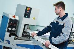 Plastikfenster und Türherstellung Arbeitskraft, die PVC-Profil schneidet Stockbild