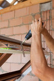 Plastikfensterinstallation Arbeitskraft befestigt Ankerplatte mit Schraubenzieher Lizenzfreie Stockbilder