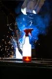Plastikflasche mit der Reinigungsflüssigkeit, die in vorderes wel CNC Mig glüht Lizenzfreie Stockbilder