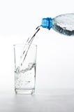 Plastikflasche und Glas Wasser Stockfotografie