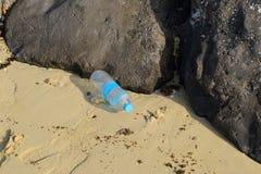 Plastikflasche weggeworfen auf einen Strand Lizenzfreie Stockbilder