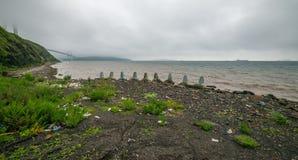 Plastikflaschen und anderer Abfall auf dem Ufer Stockfotografie