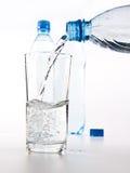 Plastikflaschen und Glas Wasser Lizenzfreie Stockfotografie