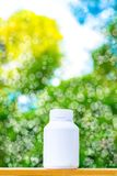 Plastikflaschenweiß auf dem Holz und Baum undeutlichen bokeh Hintergrund im Garten Unter Verwendung der Tapete für Paketarbeitsfo Lizenzfreie Stockfotografie