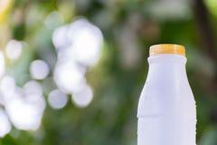 Plastikflaschenweiß auf dem Holz und Baum undeutlichen bokeh Hintergrund im Garten Unter Verwendung der Tapete für Paketarbeitsfo Stockbilder
