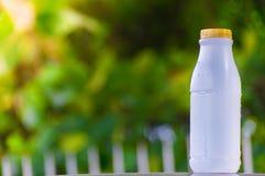 Plastikflaschenweiß auf dem Holz und Baum undeutlichen bokeh Hintergrund im Garten Unter Verwendung der Tapete für Paketarbeitsfo Stockfotos