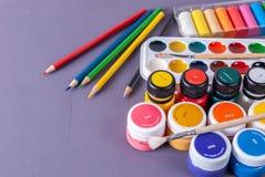 Plastikgläser mit Acrylfarbe, Aquarellen und farbigen Bleistiften Stockfoto