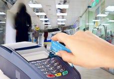 Plastikkarte der menschlichen Handholding in der Zahlungsmaschine Lizenzfreie Stockbilder
