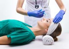 Plastikkirurgi - härlig kvinna, för kirurgi, kirurgisk kappa som ligger på sängen fotografering för bildbyråer