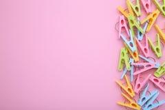 Plastikkleidungsstifte von einem rosa Hintergrund stockbild