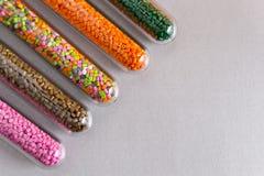 Plastikkugeln Polymerische Färbung in den Reagenzgläsern auf grauem Hintergrund Stockfotos