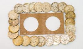 Plastikmünzen-Halter umgeben von Franklin Half Dollars Lizenzfreie Stockbilder