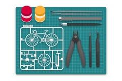 Plastikmodell mit Tool-Kit auf Schneidematte, Fahrradkonzeptdesignillustration Stockfotos