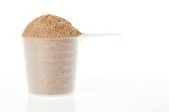 Plastikowa miarka czekoladowa serwatka odizolowywa proteinę fotografia stock