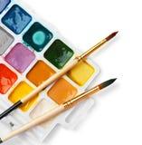 Plastikowa paleta z kolorowymi farbami i muśnięciami fotografia stock