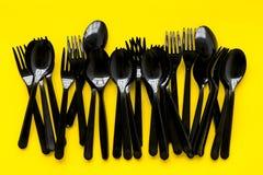 Plastikowe łyżki, rozwidlenia spożytkowanie i Ziemski ochrony pojęcie z flatware na żółtego tła odgórnym widoku fotografia royalty free