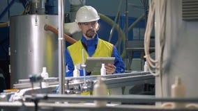 Plastikowe butelki spadają od konwejeru pod kontrolą męski pracownik zbiory