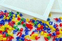 Plastikowe kolorowe szpilki z białym dziurkowanie talerzem zdjęcia stock