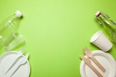 Plastikowi i Życzliwi rozporządzalni naczynia robić na zieleni rozwidlenie, noże, talerze, filiżanki i butelka, zdjęcie royalty free