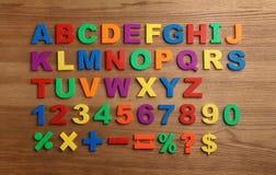 Plastikowi magnesowi listy, liczby i matematyka symbole na drewnianym tle, zdjęcie stock